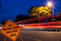 DUI / Driver license checkpoint sign with deep blue sky and car light trains in background.  Area illuminated by overhead streetlight making star.